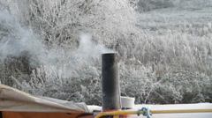 Canal boat in frozen canal with chimney smoking Stock Footage
