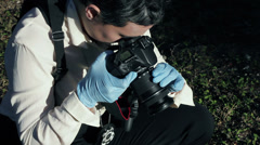 Female detective taking pictures at a crime scene 4 Stock Footage
