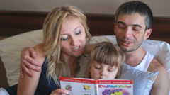 Happy family reading a book in bed - stock footage