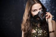 Stock Photo of elegant gorgeous young brunette woman hiding behind festive mask.