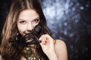 Stock Photo of portrait of a secretive elegant young bruette beauty holding festive mask.