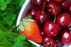 cherries and strawberry in a ceramic bowl on green grass - stock photo