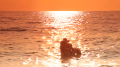 Happy couple in the sea at sunset - stock footage