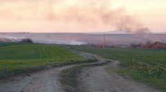 Road in Green Meadow and Gray Smoke Stock Footage