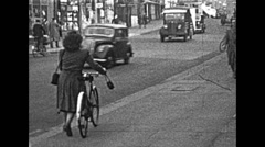 London 1948: woman riding a bycicle in the street Stock Footage