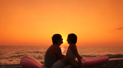 Silhoueted Couple Kissing By Sunset Stock Footage