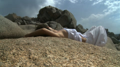 Young woman relaxing on granitic stone - stock footage