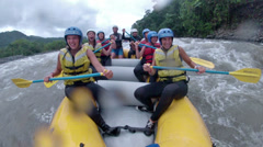 BANOS, ECUADOR - JANUARY 2014: Group of young people whitewater rafting on Stock Footage