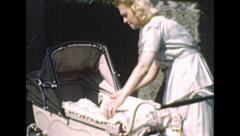 London 1948: young mother putting her baby in the stroller Stock Footage