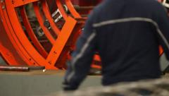 Rotating Machine with a Worker Walking Stock Footage