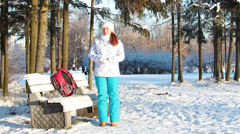 Young woman standing on a park and joying with unexpected snowfall Stock Footage