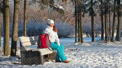 Young woman with red backpack in wintry park sitting on bench Stock Footage