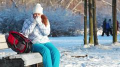 Woman blowing on frozen hands when walking in winter park Stock Footage