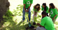 Environmental activists planting a tree in the park - stock footage
