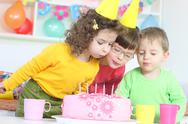 Stock Photo of Children blowing birthday candles