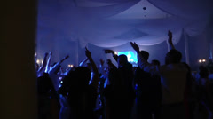 Silhouettes of concert crowd in front bright stage lights Stock Footage