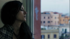 Depressed woman against wall  looking out window - stock footage