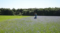 Blond girl walk blue cornflowers field. Recreation in farmland Stock Footage