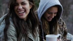 Two Teen Girls Bundled Up Outdoors, Enjoying Something On Paper Stock Footage