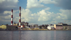 Large factory with chimney-stalks on city quay Stock Footage