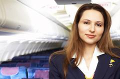 Air hostress (stewardess) in the empty airliner cabin Stock Photos