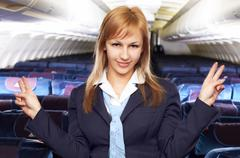 blond air hostess (stewardess) in the empty airliner cabin - stock photo