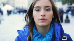 Serious beautiful girl walking in the city. She looking at camera, Slowmotion - stock footage