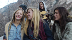 Five Bundled Up Teen Girls, One Playing Guitar, Four Waving At Friends Stock Footage