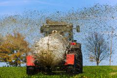 tractor fertilizes with manure a field - stock photo