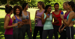 Fitness class taking a break and chatting in the park - stock footage