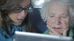 Young woman giving his grandmother a tablet PC and teaching her to use it Stock Footage
