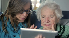 Granddoughter enjoys showing his grandmother how to use the new Tablet PC - stock footage