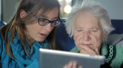 Granddaughter Teaching Grandmother How to Use a Tablet PC - stock footage