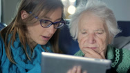 Stock Video Footage of Granddaughter Teaching Grandmother How to Use a Tablet PC