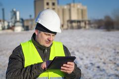 Engineer with tablet PC near the factory in winter Stock Photos