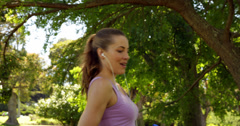 Jogger taking a break to drink water in the park - stock footage