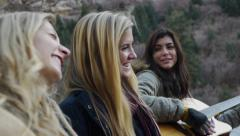 Two Blonde Teen Girls Laugh & Sway While A Cheerful Teen Latina Plays Guitar - stock footage