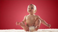 Cute baby girl sits on carpet and waves her arms in the air. Medium shot Stock Footage