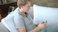 Iloinen kaveri rentouttava sohvalla käyttäen solun pone katsot kameraa ja hymyil Arkistovideo