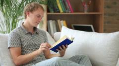 Iloinen kaveri rentoutua sohvalla lukee kirja katsot kameraa ja hymyilee Arkistovideo