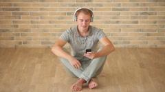Iloisia kaveri päällään kuulokkeet istuu lattialla matkapuhelimen ja hymyilevä Arkistovideo