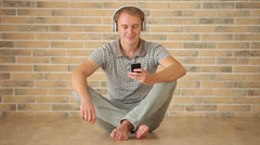 Happy guy wearing headphones sitting on floor using cell phone looking at camera - stock footage