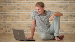 Young man sitting on floor using laptop loooking at camera and smiling Stock Footage