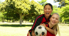 Female football teammates celebrating a win in the park Stock Footage