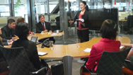 An Asian businesswoman leads a meeting in the middle of a large round table Stock Footage