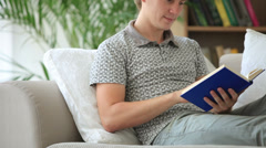 Happy guy sitting on sofa reading book looking at camera and smiling. Panning Stock Footage