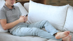 Handsome guy relaxing on sofa using cell phone loooking at camera and smiling Stock Footage