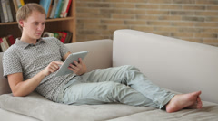 Handsome young man relaxing on couch using touchpad and smiling Stock Footage