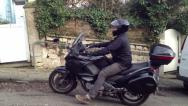 Stock Video Footage of Motorbike courier arrives fast on large cruiser type bike version 2.