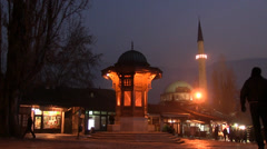 People are walking near Sebilj and the mosque in Sarajevo Stock Footage